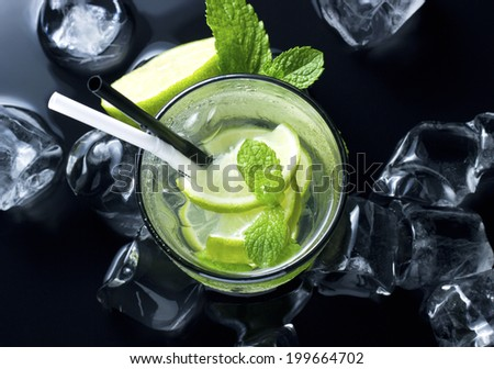 Mojito cocktail with fresh limes, mint and ice on black table - stock photo