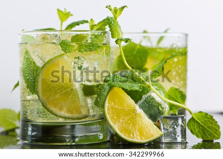Mojito cocktail with fresh limes, mint and ice, selective focus - stock photo