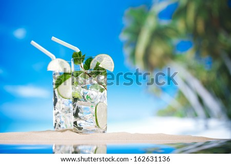 mojito cocktail with ice, rum, lime and mint   in a  glass  on beach sand and  blue stars background - stock photo