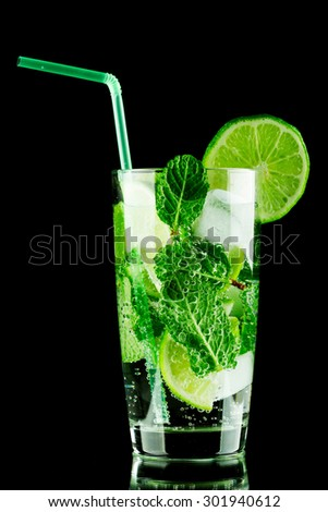 Mojito cocktail with lime, mint and ice on black background  - stock photo