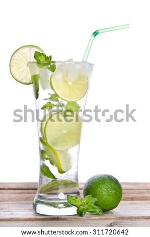 Mojito cocktail with lime on wooden table
