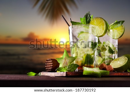 Mojito drinks on wood with evening blur ocean shore background - stock photo