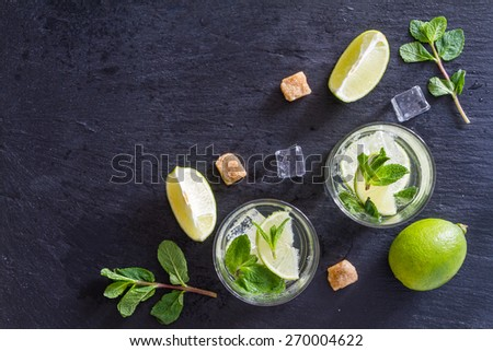 Mojito ingredients - lime, mint, sugar, rum, ice, dark stone background, top view - stock photo