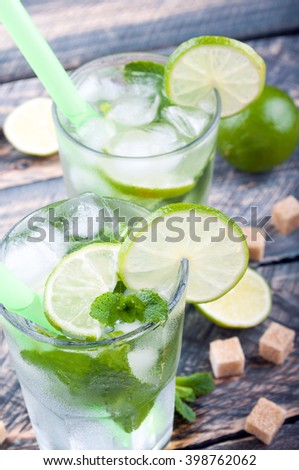 Mojito lime drink cocktail in bar on rustic table. Closeup. Ingredients for making mojito. Selective focus.  - stock photo