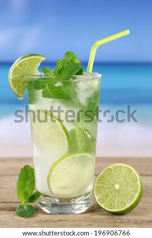 Mojito or Caipirinha cocktail with fruits on the beach while on vacation - stock photo