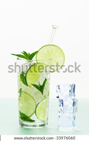 Mojito with ice, lime and mint on frosted glass table - stock photo