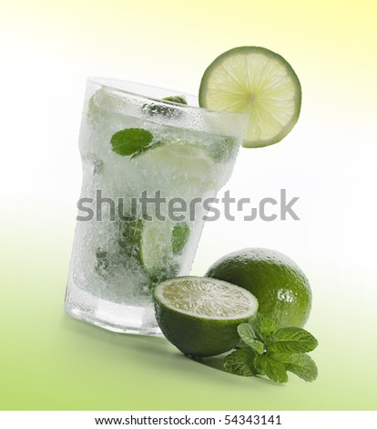 Mojito with limes and mint on green background - stock photo