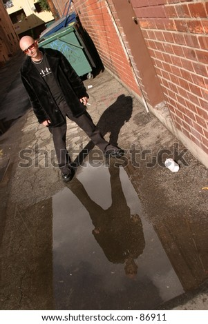 Mojo El Diablo stands in an alley with his reflection in a puddle of water and his shadow behind him