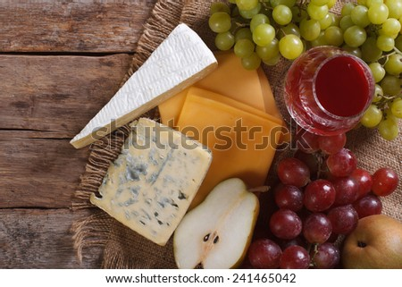 Molded cheese, wine and fruit on the table close-up. horizontal view from above  - stock photo