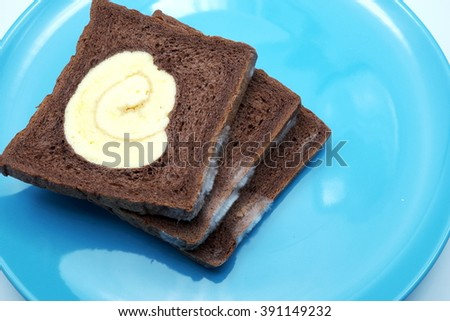 Moldy bread, chocolate bread with vanilla roll at center on blue plate. Focus on mold. Space for texts. - stock photo
