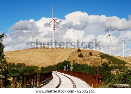 Molise rural landscape with railroad, wind turbines and moody sky - stock photo