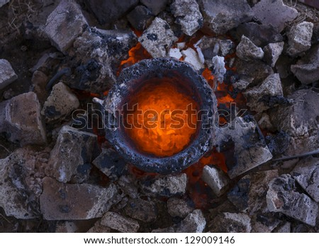 Molten bronze in a crucible awaits casting