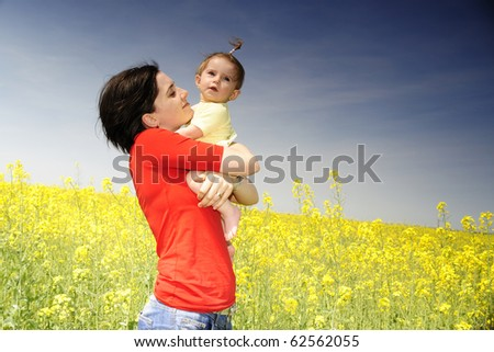 Mom and baby girl in a rapeseed field - stock photo