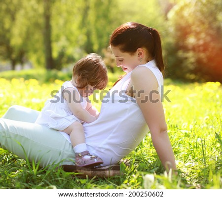 Mom and baby having fun on grass in the summer park - stock photo