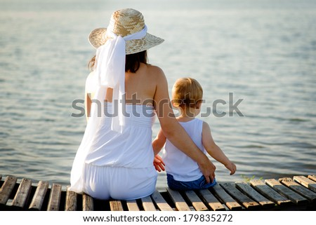 mom and baby resting on the bank near the water - stock photo