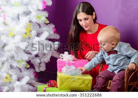 Mom and baby son pile presents under the Christmas tree - stock photo