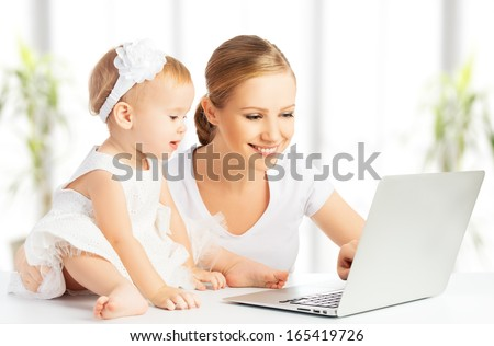 Mom and baby with laptop computer working from home - stock photo