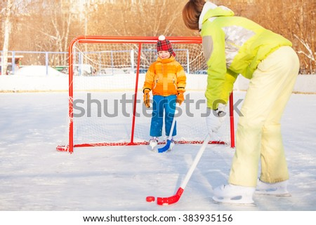 Mom and boy play ice hockey outside on playground - stock photo
