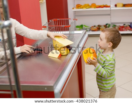 Mom and boy playing in the shop. role-playing. small child playing in the supermarket to buy food. smiling woman behind the counter helps the boy to make a purchase - stock photo