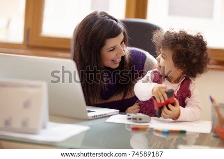 Mom and businesswoman working with laptop computer at home and playing with her baby girl. Horizontal shape, front view, waist up - stock photo