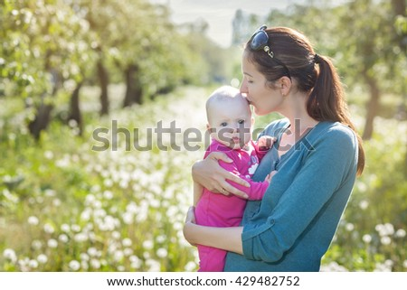 Mom and child in the garden. Mom holding the baby in his arms and kisses