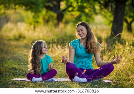 Mom and child in the lotus position on the nature - stock photo