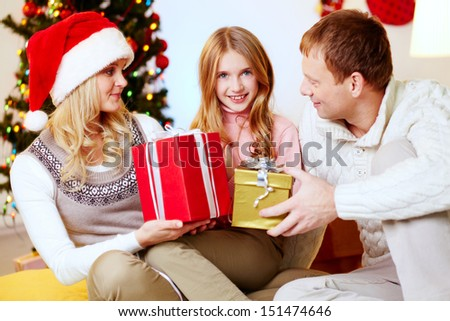 Mom and dad giving presents to their daughter wishing merry Christmas - stock photo