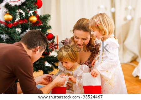 Mom and dad looking with twins daughters inside of Christmas socks near Christmas tree - stock photo
