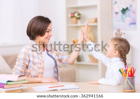 Mom and daughter are high-fiving each other.