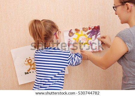 Mom and daughter are trying to hang a picture on the wall