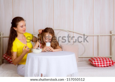 Mom and daughter at the table. daughter drinking milk - stock photo