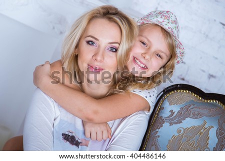 Mom and daughter blonde caucasians are happy and smiling in a white room. Girl having fun with her mom. Beautiful smile. Happy beautiful family. Mothers Day - stock photo