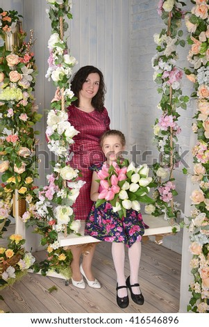 Mom and daughter caucasians are happy and smiling in a white room. Girl having fun with her mom. Beautiful smile. Happy beautiful family. Mothers Day - stock photo