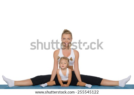 Mom and daughter do gymnastics on blue mat - stock photo