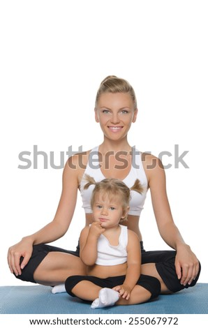Mom and daughter doing yoga on blue mat - stock photo