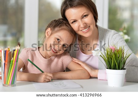Mom and daughter draw and smile - stock photo