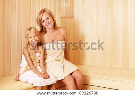 Mom and daughter in the sauna - stock photo