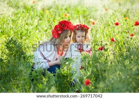 Mom and daughter in traditional Ukrainian costume in the forest - stock photo