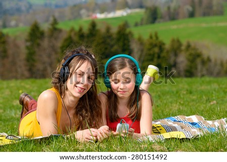 Mom and daughter listening music in nature