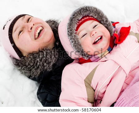 Mom and daughter lying on a snow, laughing - stock photo