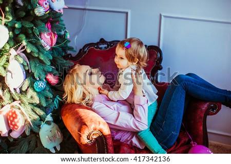 Mom and daughter near Christmas tree - stock photo