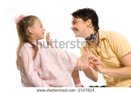 mom and daughter playing tickling on white background - stock photo