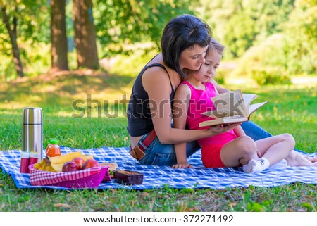 Mom and daughter reading a book on the lawn in the park - stock photo