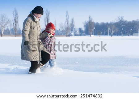 Mom and daughter running in the snow/Mom and daughter running in the snow - stock photo