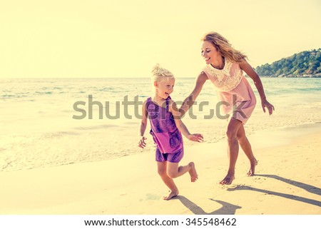 Mom and daughter running on the beach - Family moments, beautiful young mother trying to catch her daughter, having fun and enjoying summer holiday - stock photo