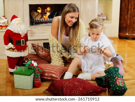 Mom and daughter siting in front of a fireplace - stock photo