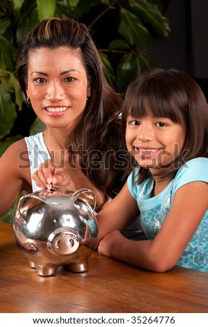 mom and daughter smile at the camera as they pose with a piggy bank - stock photo
