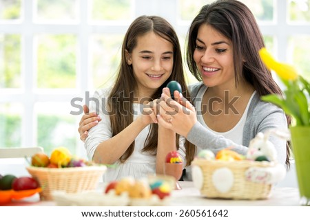 Mom and  daughter together painting Easter eggs - stock photo