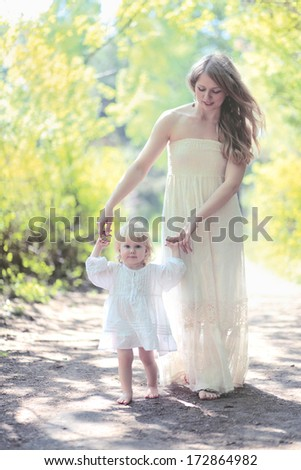 Mom and daughter walking in the forest sunny summer day