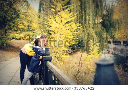 Mom and daughter walking in the park in autumn - stock photo